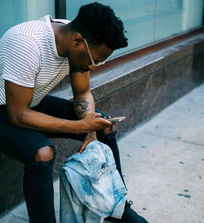 make-friends-as-an-adult-after-30-in-a-new-city-black-man-on-phone