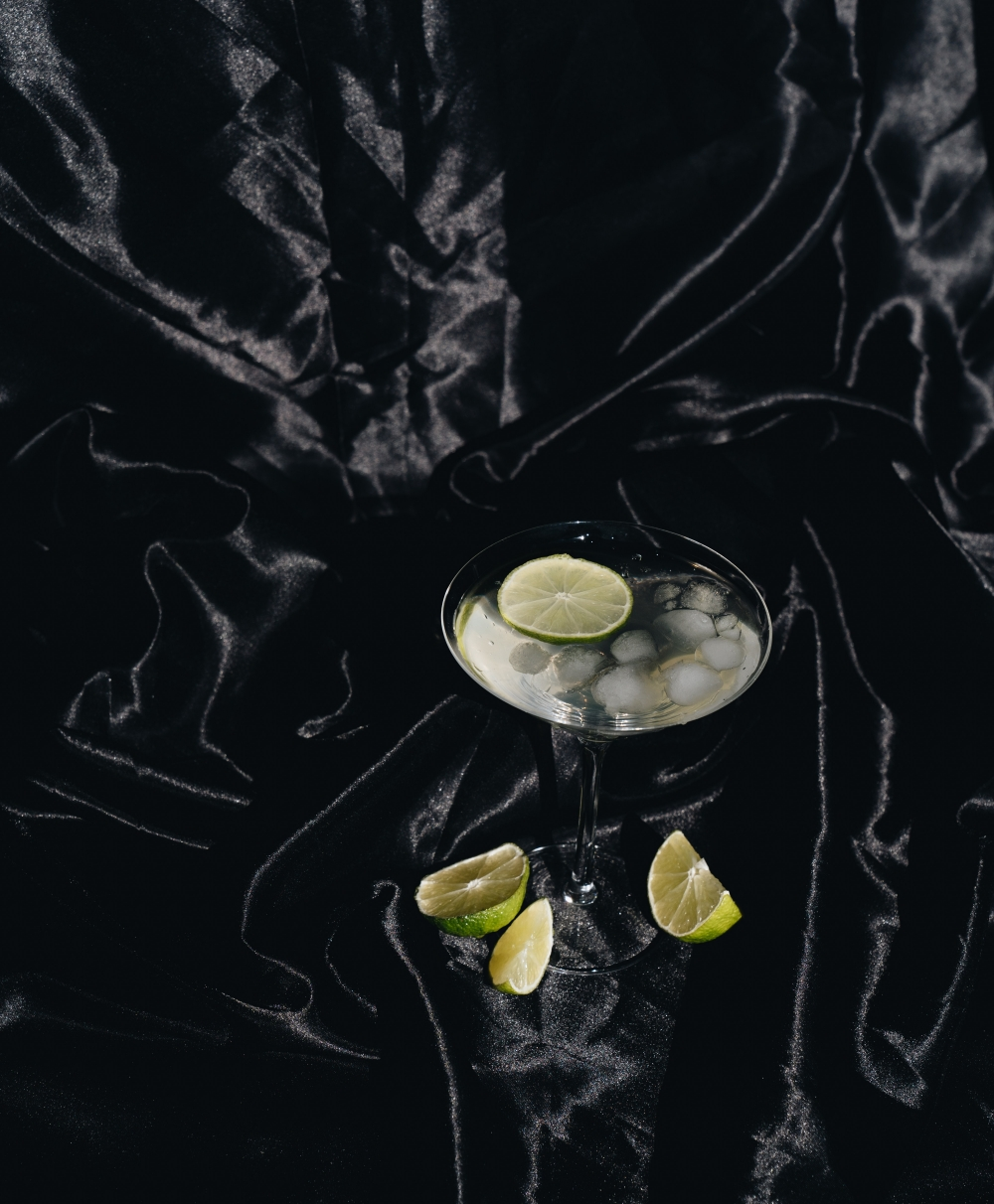 nye-new-years-eve-2020-alone-low-key-at-home-photo-of-cocktail-glass-on-black-silk-fabric